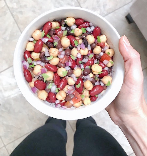 Cowboy Caviar in a bowl being held by Christina Carlyle